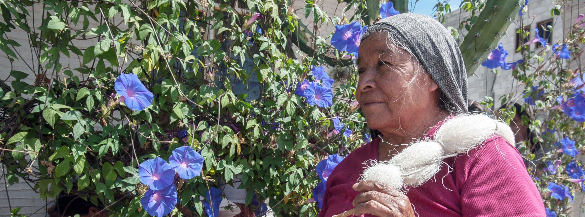 Woman stands next to tree with purple flowers holding woven fibers over her shoulder
